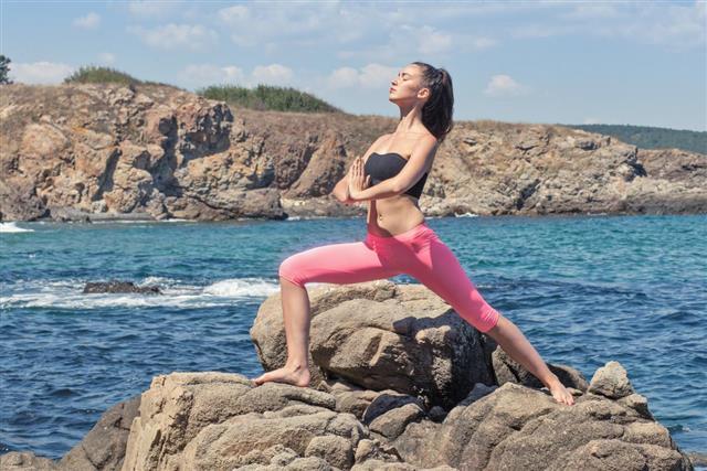 Young brunette woman doing yoga on rocky coastline