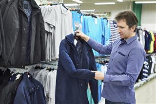 Man chooses jacket in supermarket