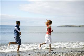 Children Running Barefoot On Beach