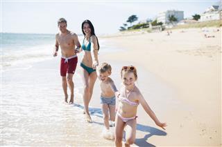 Happy Family In Swimsuit Having Fun
