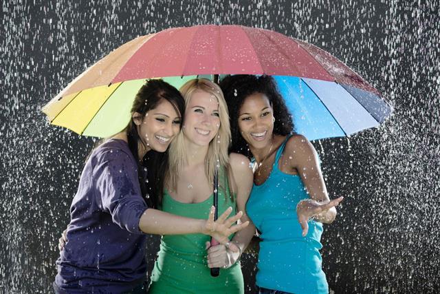 Three Women With Umbrella Enjoying Rain