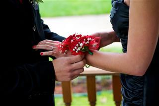Man Applying Corsage To Woman Wrist