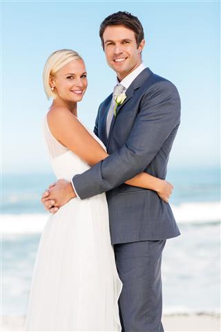 Loving Newlywed Couple Embracing On Beach