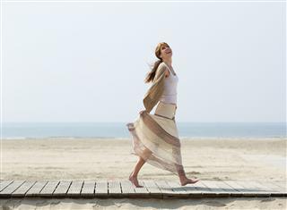 Mature Woman Walking Barefoot At Beach